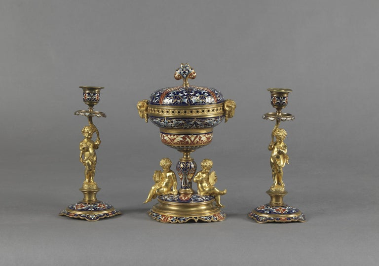 A fine gilt-bronze and champlevé enamel garniture set comprising a pair of candelabra and a brûle-parfum and cover. 