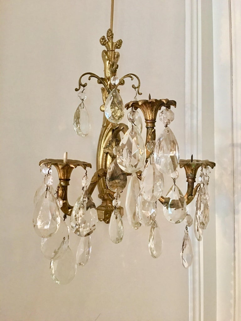 Delightful pair of 3-branch Louis XV style gilt bronze and crystal pendant wall sconces. Each candle arm features candle holders (bobèches) in the form of a blooming flower. Candelight is gently reflected by hanging crystals. Non-electrified.