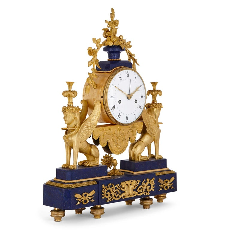 This exquisite early 19th century mantel clock is mounted with gilt bronze and has benefited from the addition of a later lapis lazuli veneer. The clock is formed of a cylindrical clock drum inset with a circular dial inscribed with Roman numerals.