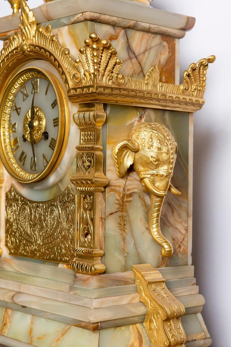 Gilt bronze and onyx garniture. Orientalist style, France, circa 1890. Dimensions of the clock: 60 cm height, 20 cm depth, 37 cm width.
