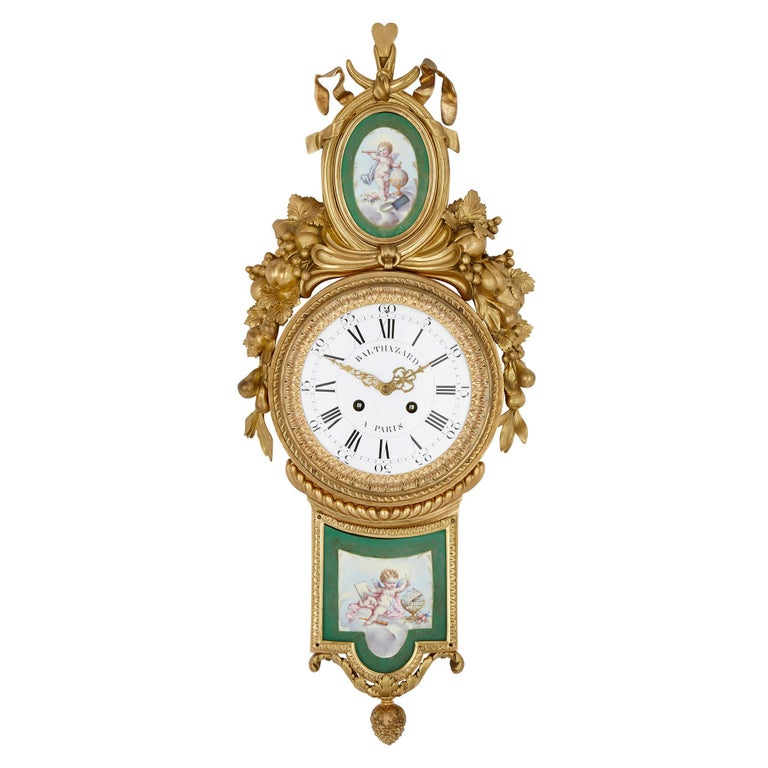 This wall clock and barometer pair are contained within identical gilt bronze cases, feature identical gilt bronze mounts, and are inset with matching porcelain plaques. The circular dial of each piece is crafted from enamel, the clock dial