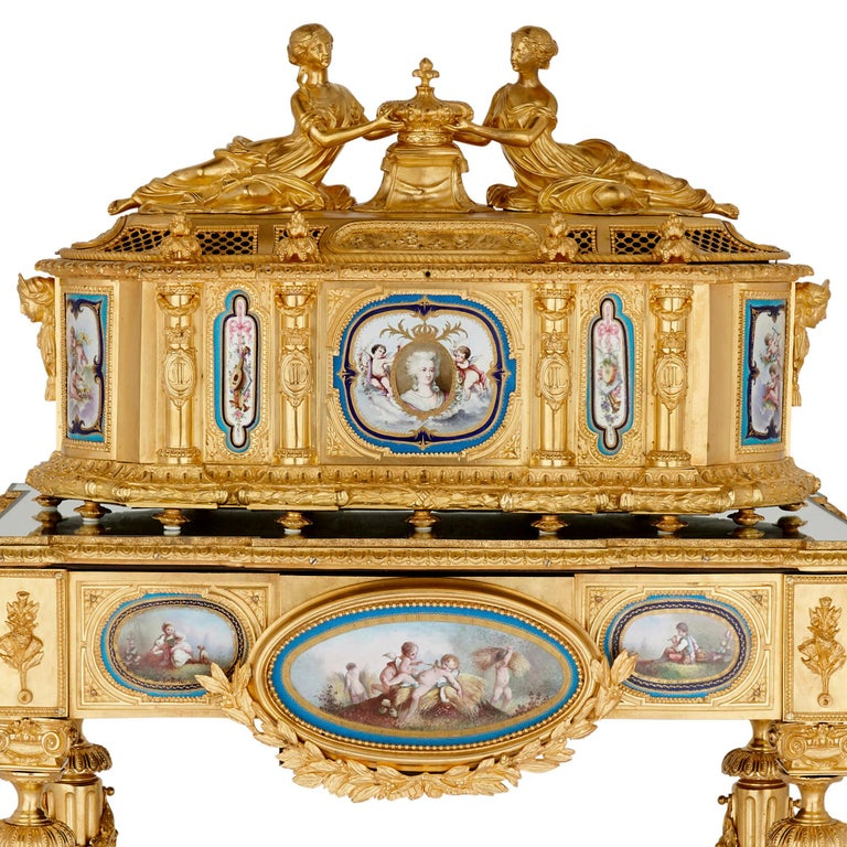 Gilt bronze and Sèvres style porcelain Louis XVI style casket on stand  This magnificent Louis XVI style ormolu casket is supported by a mirror-topped table stand, which sits on four tapered, fluted legs connected by a curving X-form stretcher. In