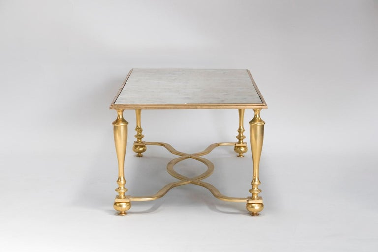 Rectangular gilt bronze coffee table with baluster shaped legs joined by a sinuous stretcher X shaped. Oxidized mirror upper tray. One spot on the mirror visible on pictures. Work from the 20th century, made circa 1940.