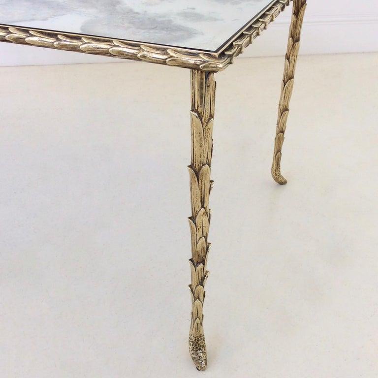 Nice gilt bronze coffee table by Maison Baguès, circa 1950, France. Palm trunk motif frame and oxidized mirror. Dimensions: 102 cm W, 48 cm D, 40 cm H. Good condition.
