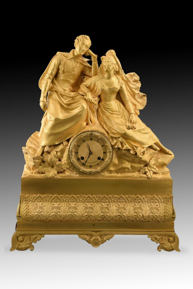 Table clock. Ormolu. XIX century.  Machinery in working order.  Table clock with box made of gilt bronze, and Paris machinery in working order. The base is raised on legs decorated with vegetal and architectural elements of clear classicist