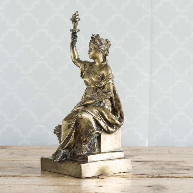 A gilt bronze model of Ceres, Roman goddess of agriculture, modeled seated holding torch aloft in one hand and with a sheaf of wheat in the other, on plinth base, Italian, 19th century.  This particular model of Ceres appears to be strongly