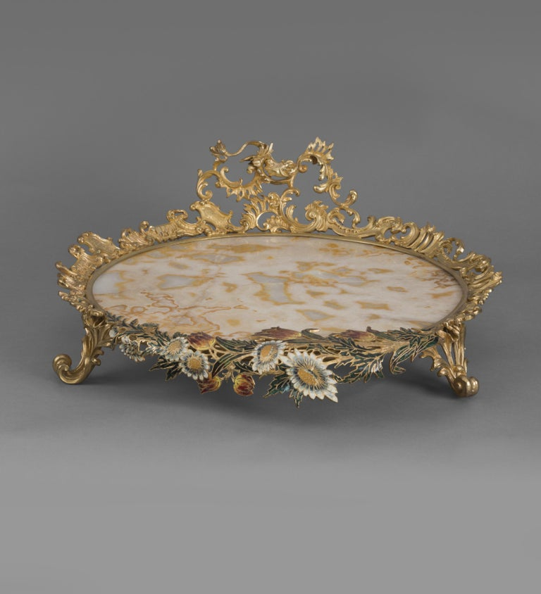 An unusual gilt-bronze mounted champlevé enamel, alabaster fiorito centrepiece.  French, circa 1900.   This unusual centrepiece has a circular alabaster fiorito base within an elaborate rococo-cast gilt bronze border with C-scrolls, scrolling