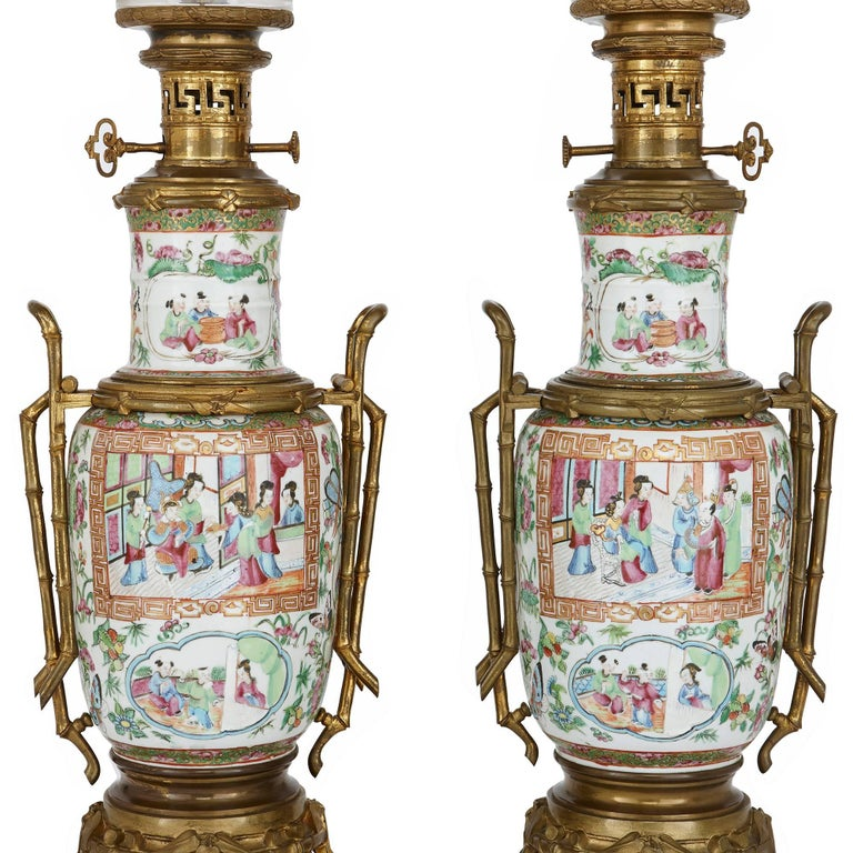 These elegant lamps are crafted from Chinese Canton famille rose porcelain and mounted with French gilt bronze (ormolu). The lamps feature beautiful vase-form porcelain bodies, which are finely painted with Chinese court scenes, as well as flowers,