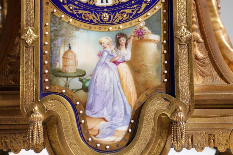 Beautiful 18th century Rococo manner gilt bronze mantel clock with elegant Sèvres style bleu / navy colored porcelain. The porcelain is very delicately hand painted with a landscape on one side of the vases and figures on a staircase on the