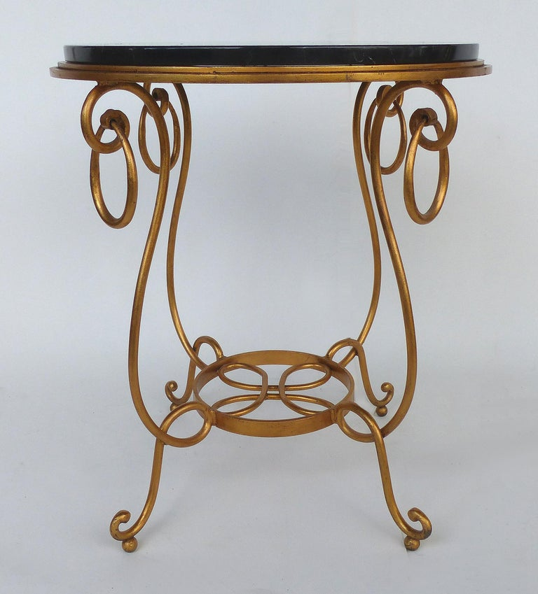 Offered for sale is a gilt wrought iron occasional table fitted with a thick round black marble top. The table has a delicate feel with lovely curves even though the materials are substantial.