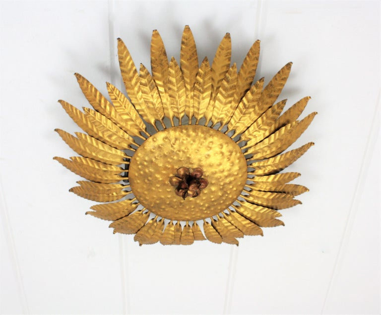 A highly decorative handcrafted gilt iron flower burst ceiling sconce or wall light fixture. It has a beautiful decoration with leaves and a decorative detail in the center of the fixture. Gorgeous light effect when lit. Gold leaf finish and