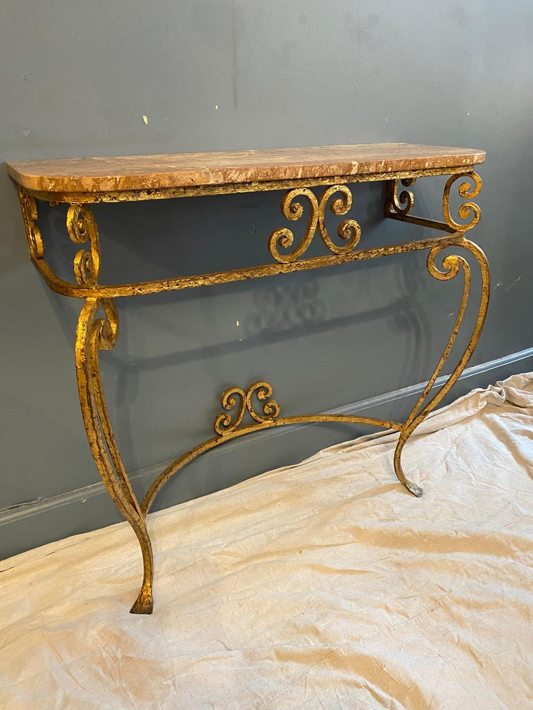 Nice gilt iron Italian marble topped console and matching mirror. Perfect for your entrance or hallway! Gilt is in great shape with minor losses to finish. Marble top has a chip to back right side and there are areas where marble was filled, but