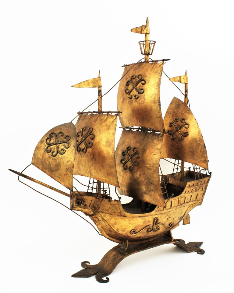 Outstanding large sized gilt wrought iron Spanish caravel boat or galleon sculpture. In the style of Gilbert Poillerat designs. This sailing ship sculpture was handcrafted in Spain at the mid-20th century period. The ship stands up on a