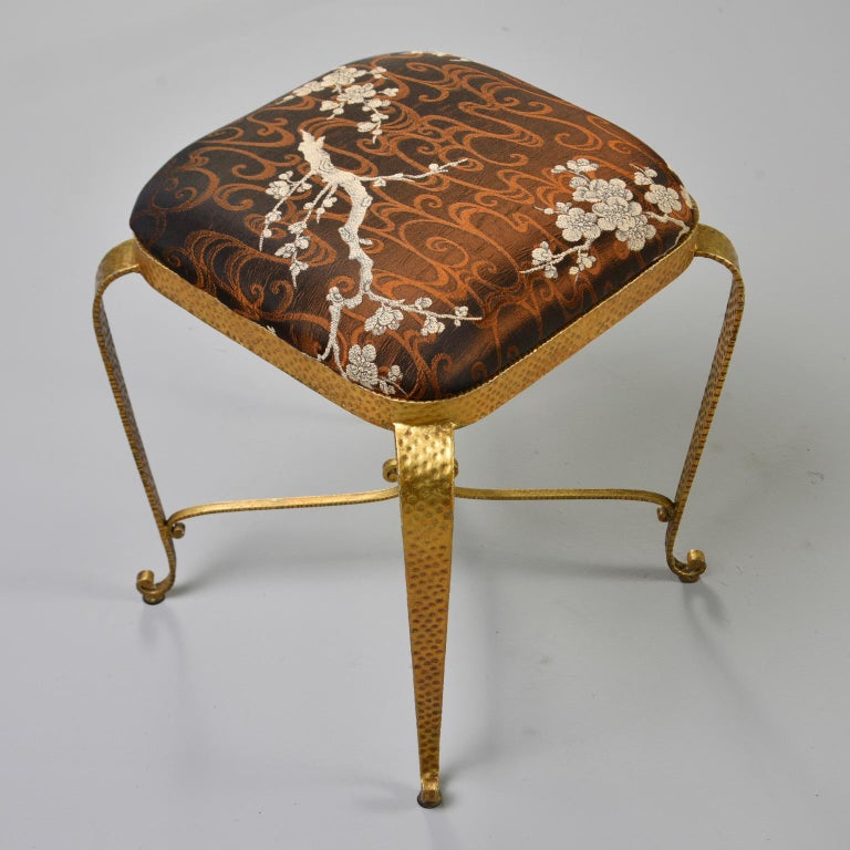 Italian gilt iron frame stool features a hammered surface texture, X-form stretcher with scrolled top, curved feet and upholstered seat in a bronze colored Asian brocade, circa 1960s. Unknown maker. Sold and priced individually. Two stools available