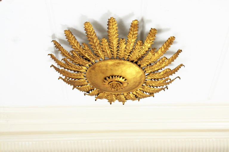 Beautiful hand-hammered gilt iron flower burst wall sconce or ceiling fixture with scalloped leaves in two sizes surrounding a central sphere adorned by a sunflower decoration. It can be used as a flush mount or as a wall light fixture, Spain,