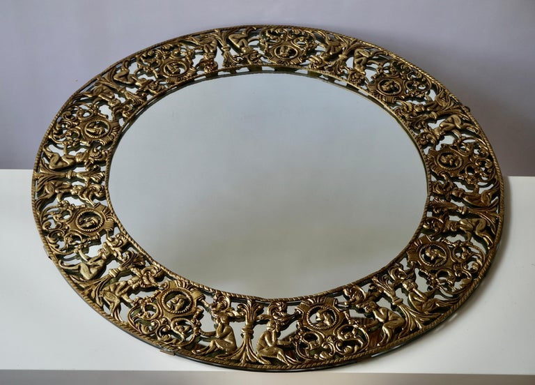 Beautiful large handcrafted gilt iron sunburst mirror. Italy, 1960s.The wall mirror has figural and leaves surrounding a central round glass.  Overall diameter: 77 cm  Diameter of the inside glass: 52 cm.