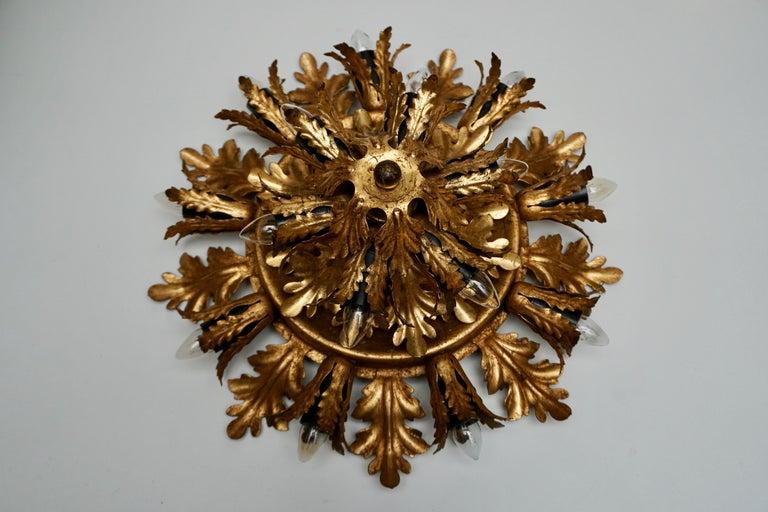 "Gilt metal sunburst flush mount or sconce, Italy. Materials: Gold ""antique"" painted metal (iron) presenting European oak leaves (quercus robur) and ferns. Bakelite sockets. Measures: Diameter 42 cm, depth 18 cm. Fifteen E14 bulbs."