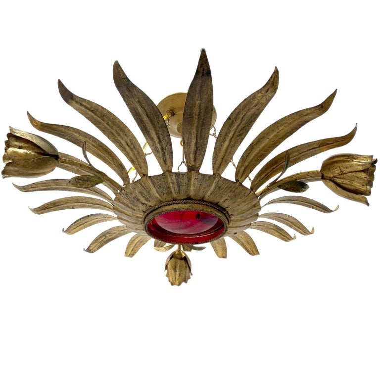 A circa 1950s gilt metal sunburst light fixture with four interior candelabra lights, one light in each flower and original ruby red glass inset.  Measurements: Diameter: 24