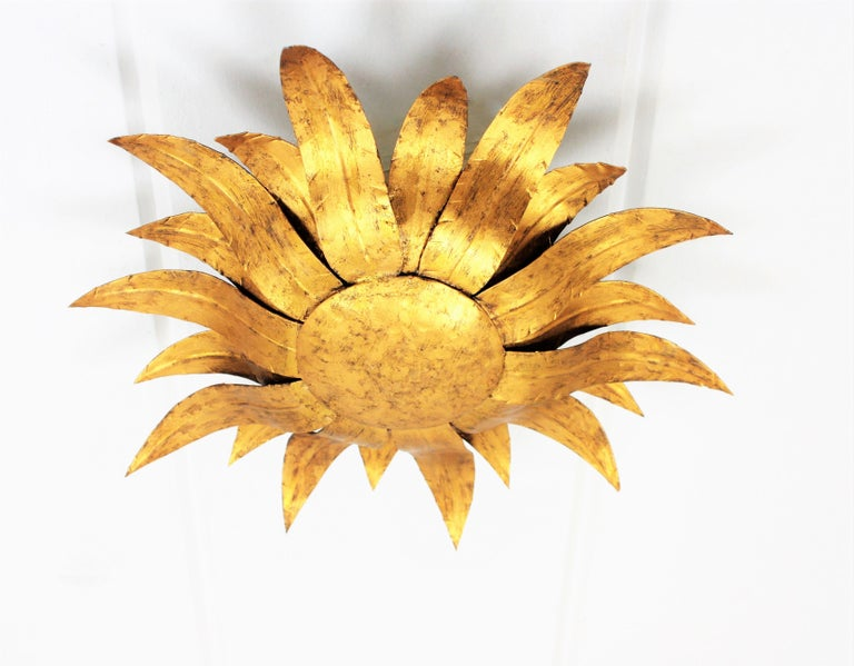Lovely hand-hammered flower burst gilt iron sconce with gilt finish. This piece can be placed as ceiling fixture but also as wall sconce, Spain, 1960s. Dimensions: H 16.14 in x W 16.14 in x D 4.33 inches.