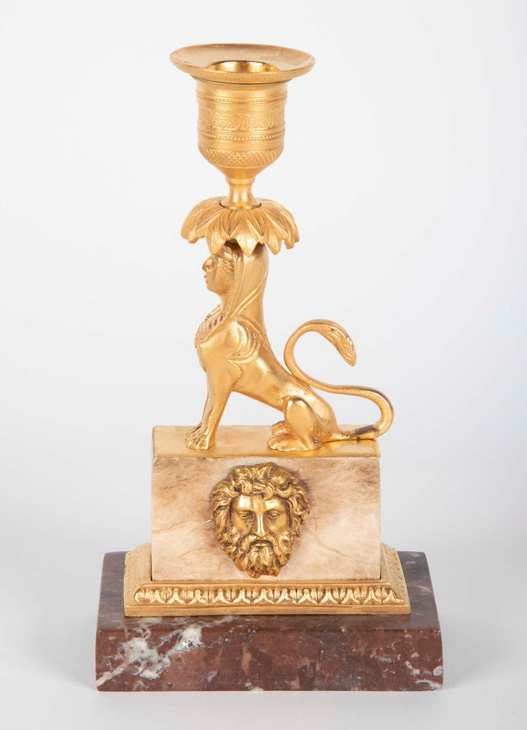 A gilt bronze candlestick on stepped marble base with gilt bonze face of a classical figure mounted on it.