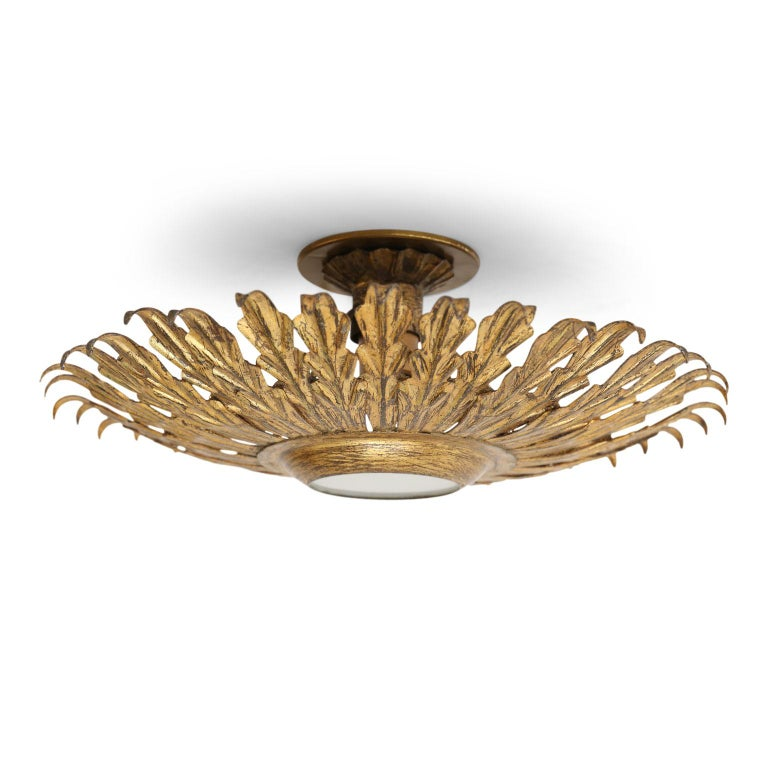 Gilt tole flush mount light for your ceiling or wall. Sunburst design of gilt tole leaves radiating from frosted glass shade. This vintage Spanish light dates from about 1950-1970 (Barcelona) and is newly wired for use within the USA. Accommodates a
