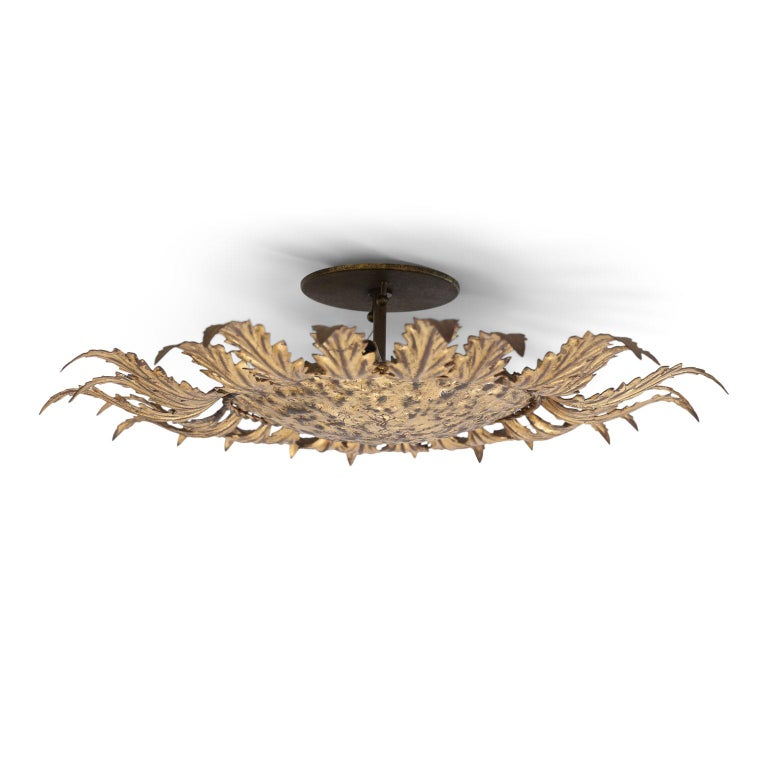 Gilt tole flush mount light for your ceiling or wall. Sunburst design of gilt tole leaves radiating from a gilded hammered tole disc. This vintage Spanish light dates from about 1950-1970 (Barcelona) and is newly wired for use within the USA.