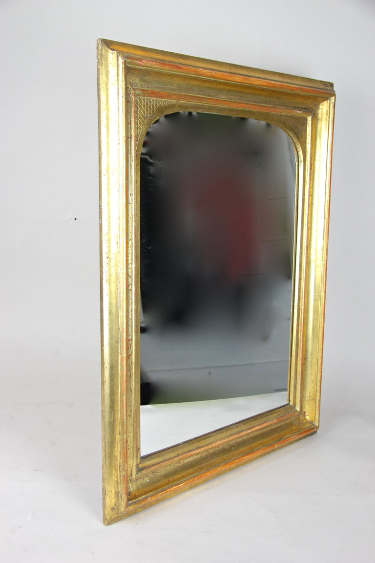 Remarkable gilt wall mirror from the early Biedermeier period in Austria, circa 1825. In an absolute fantastic original condition, no former restorations (we just had to renew the mirror glass) and covered with fine gold leaf on red Bolus which you