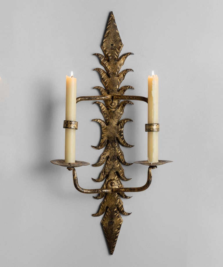 Decorative gilt metal candle lit wall sconce.