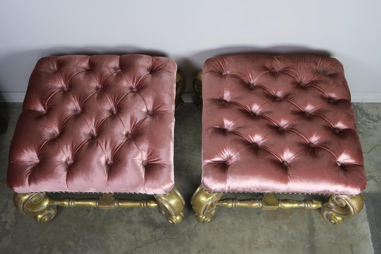 Pair of French style giltwood benches standing on four cabriole shaped legs that are connected by a bottom stretcher. The benches are upholstered in a beautiful pink tufted velvet and detailed with custom nailhead trim.