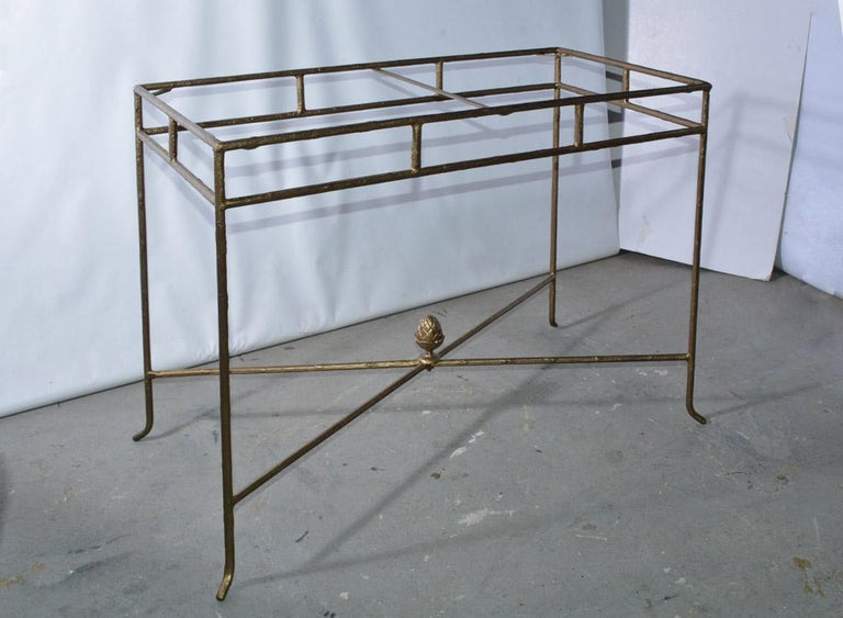 The contemporary console table has a gilt wrought iron structure with a branch-like texture and a frosted glass top inset into a frame and held in place by a center and corner braces. A stylized acorn embellished the crisscross braces. Wonderful for