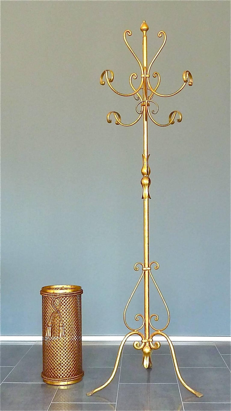 A beautiful Italian Midcentury gilt wrought iron and metal coat stand or hat rack in the style of Piero Fornasetti and Hans Kögl, Italy, circa 1950s. The coat stand which has a width of about 56 cm / 22.05 inches and which is 185 cm / 72.83 inches
