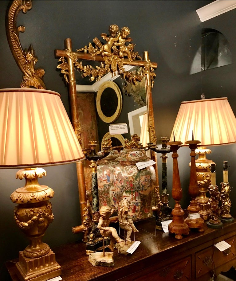 A faux bamboo mirror, primarily water gilt with lots of rich red bole bleeding throughout . The top an allegory of peace, cherubs embracing (as in friendship ) upon the instruments of war. The top bamboo stalk hung with floral festoons.  Usual dirt,