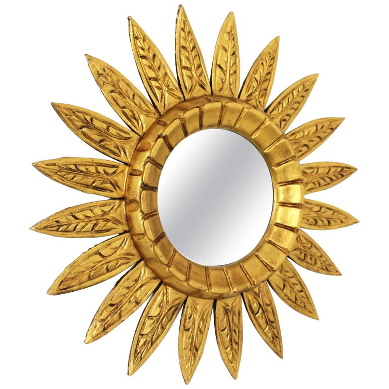Spanish Mid-Century Modern carved giltwood sunburst flower mirror, Spain, 1950s-1960s. A lovely midcentury flower shaped sunburst mirror with gilt finish. It has beams with carved decorative details and a carved frame pattern surrounding the