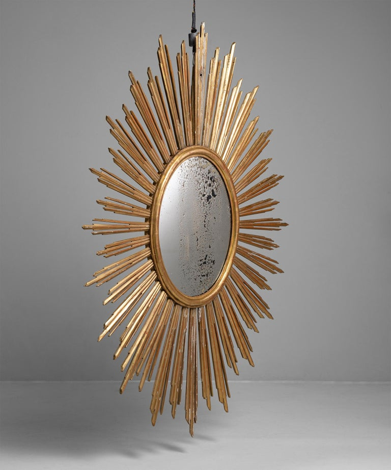 """Giltwood sunburst mirror, France, circa 1800  Beautifully carved gilt wooden frame with original foxed mirror plate.  Measures: 81.5"""" W x 62.5"""" D x 2.75"""" H  $ 18,500."""