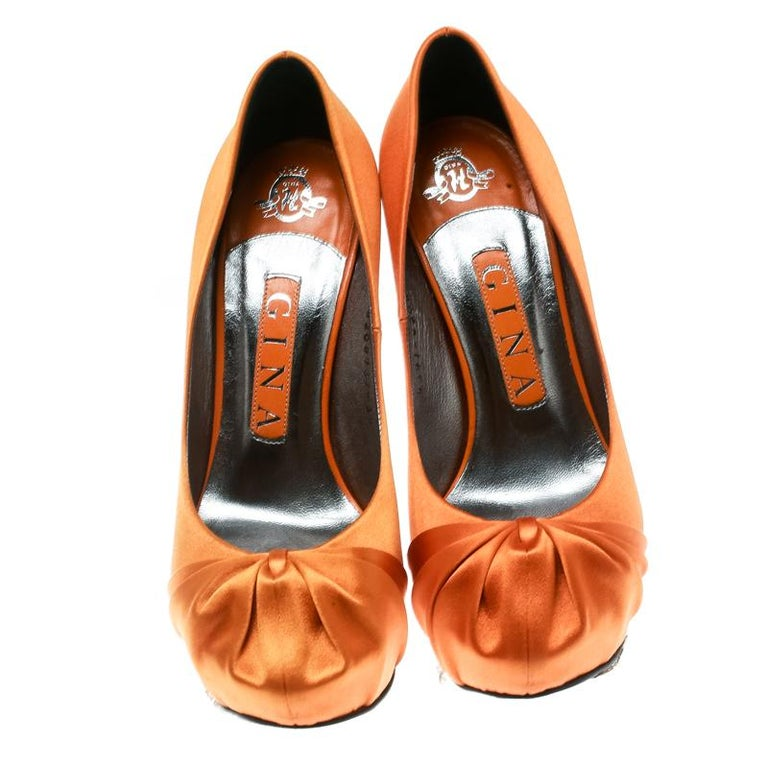Picture how these Gina pumps will beautifully make you dazzle at every step, and fetch admiring gasps your way every time you sashay out. The pumps carry a glorious orange exterior made from satin, while their insoles are lined with leather. The