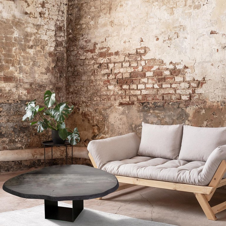 A sculptural side table crafted in centenary solid ginkgo biloba wood on an iron base, the Ginkgo Machia table is a celebration of natural wood. Proudly displaying its cracks, veins and movement, the table's surface is coated with epoxy resins and