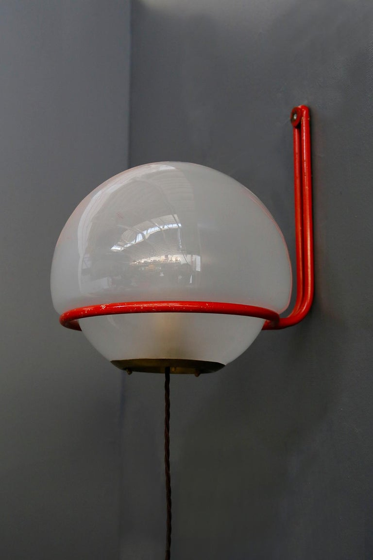 Important and published wall lamp of 1950s. The lamp is designed by Gino Sarfatti for Arteluce. The ceiling lamp is in satin glass with a rounded shape. To support it on the wall there is a red painted aluminium tube that surrounds the sphere. The