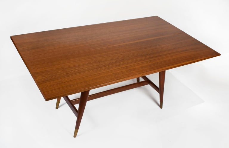 Vintage Model 2134 Italian walnut flip-top table designed by Gio Ponti for M. Singer & Sons. Two book-matched Italian walnut tops with beveled edges connected with recessed hinges over solid walnut tapering legs with brass sabots. The tops easily
