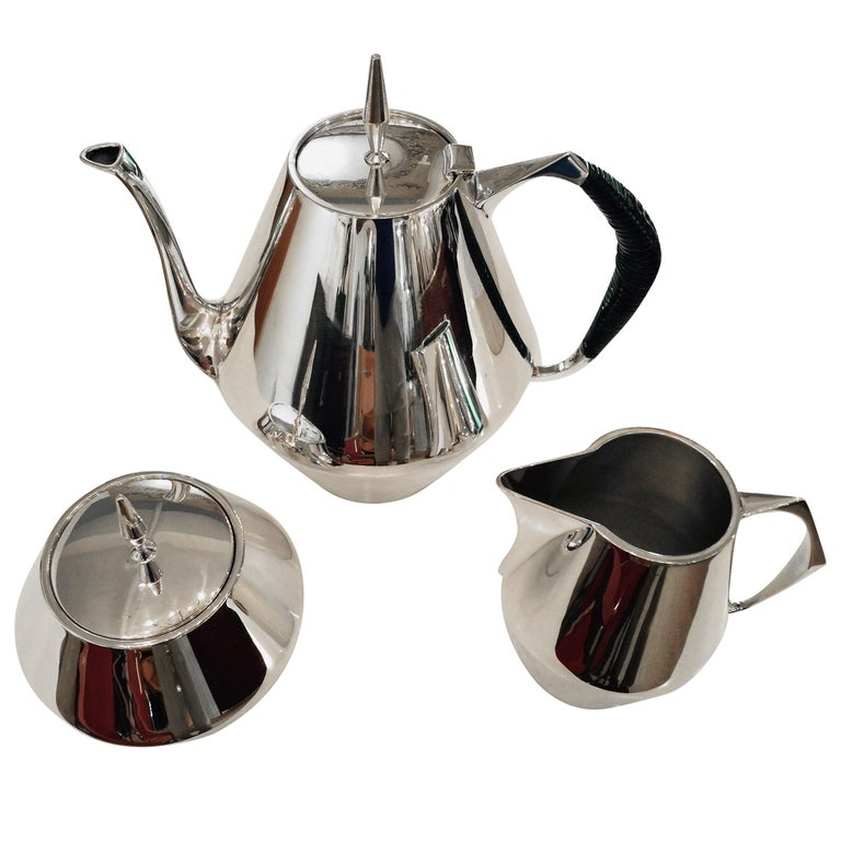 Three-piece Tea serving set in sterling silver designed by Gio Ponti for Reed & Barton in the Diamond pattern. USA, circa 1950.   Includes a tea pot, creamer and sugar jar. Tea pot and sugar jar are lidded. Tea pot features black cane-covered