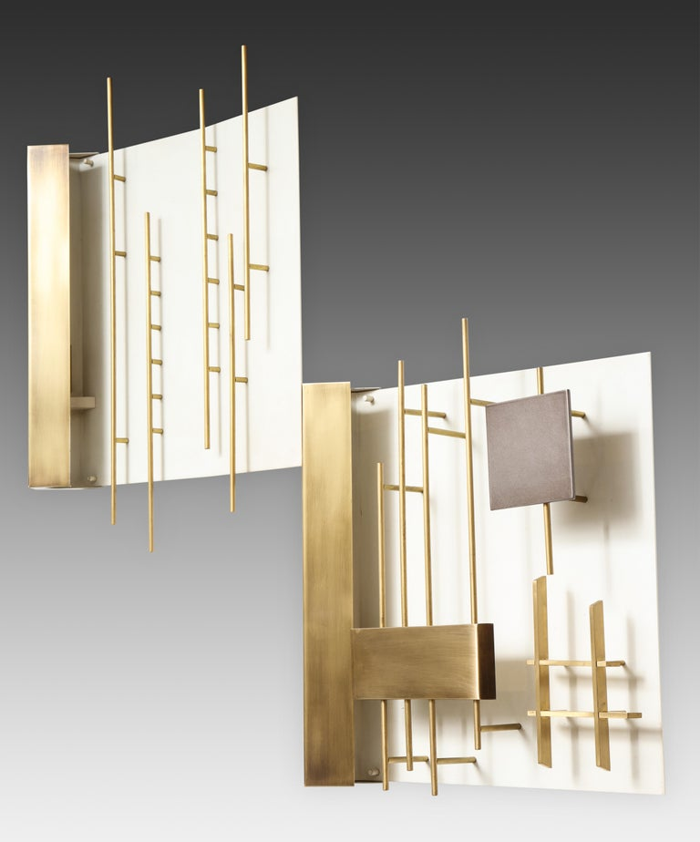 Designed by Gio Ponti for Lumi, rare pair of first edition 'Quadri Luminosi' sconces models 575 and 576, Italy, circa 1960. Brass and enameled brass architectural rods and geometric shapes sculpturally mounted on white enameled metal. The light