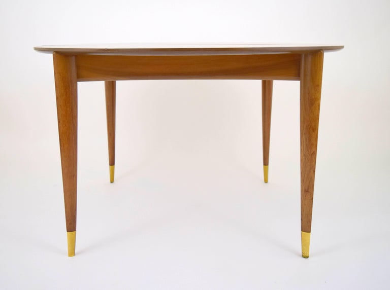 "Graceful Gio Ponti walnut dining table for M. Singer and Sons. Beautiful graining throughout, elegantly tapered triangular form legs with solid brass ferrules, gently concaved apron. Four 14"" leaves included and removable centre support legs, allows"