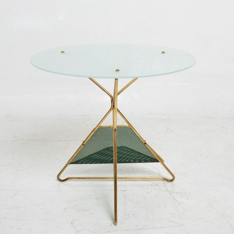 Gio Ponti vintage Mid-Century Modern round side table with built in magazine holder rack, Italy, circa 1950s. Table made with a fabulous sculpted brass base and frosted round glass top. The base has a perforated green metal magazine holder (green