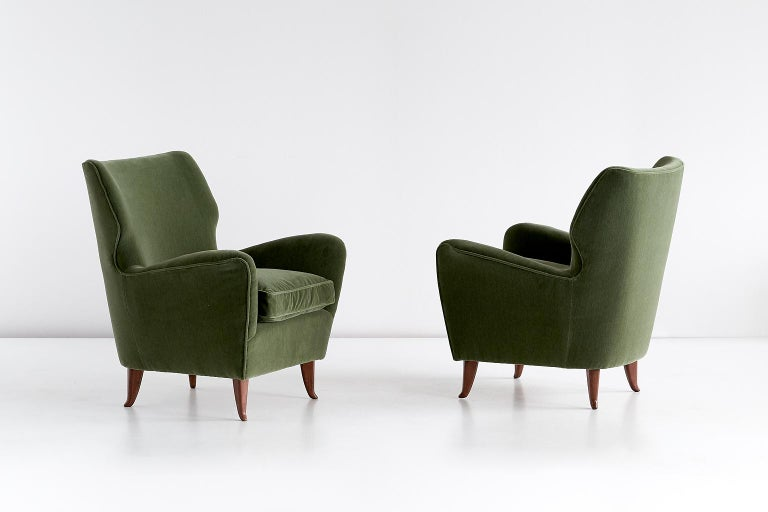 This pair of armchairs was designed by Gio Ponti in 1949. This particular model was manufactured for the Hotel Bristol in Merano, Italy.  The rounded lines and the curved, tapered legs in walnut wood give the chair a refined appearance. The chairs