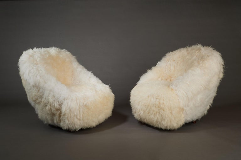 Gio Ponti (1891 - 1979)  A stunning pair of armchairs by Gio Ponti, upholstered in soft, ivory-colored longhaired lamb's wool, set on tapered mahogany legs. The stark simplicity of the design, cozily rounded construction, and lush textured sheepskin