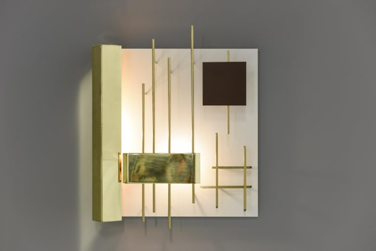 Elegant square wall sconces by the one of the famous designer and architect from Italy. Very graphic lamps in brass and metal lacquered. The light hidden on the left side creates play of light on the lamp and wall.  Signed with applied brass