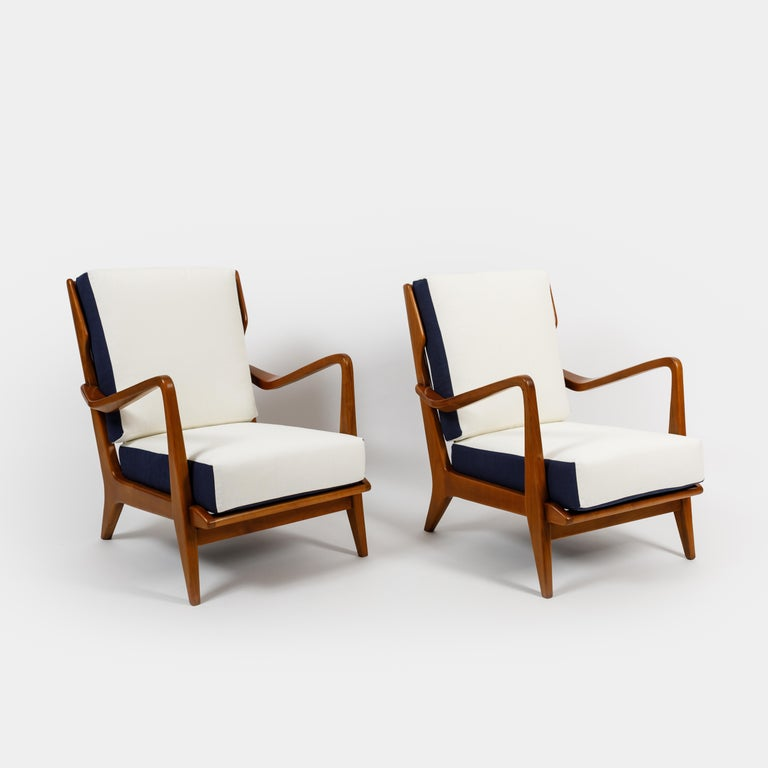 Designed by Gio Ponti and manufactured by Cassina model 516 pair of sculptural armchairs or lounge chairs, with white and navy cotton linen upholstered cushions on walnut frames, Italy, 1950s. Great architectural details in the frame including