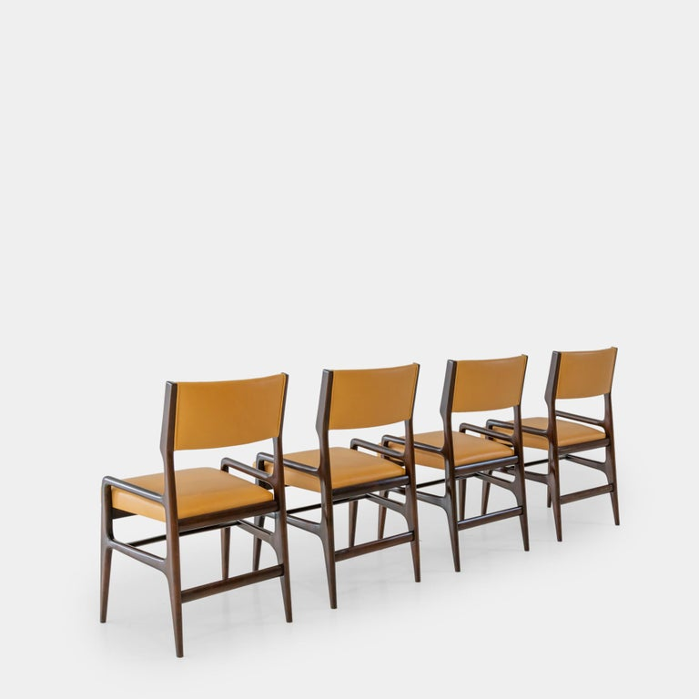 Designed by Gio Ponti and manufactured by Cassina for Altamira, New York, a very rare set of four dining chairs model AP 1676, circa 1953. These beautifully sculptural chairs have architectural walnut frames and are newly upholstered in a sumptuous