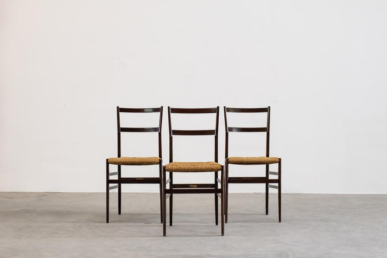 Very rare set of three Superleggera chairs designed by Gio Ponti in 1957 for Cassina. First edition of this iconic model with a structure in varnished wood and seat in braided rope. Cassina brass labels are present on the chair structure.