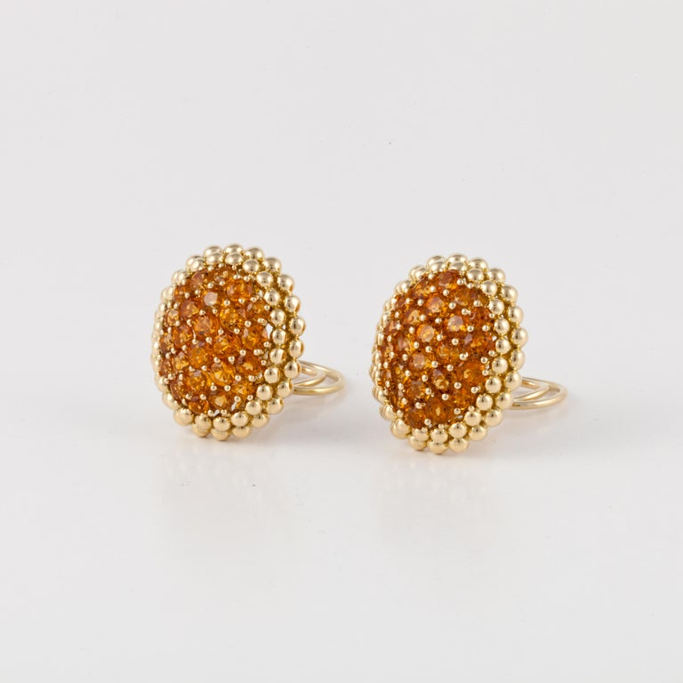 18K yellow gold earrings by Gioeil Moda.  They hold a total of fifty (50) citrines which are prong set.  There are two rows of small balls around the outer edges.  Measure 1-1/8