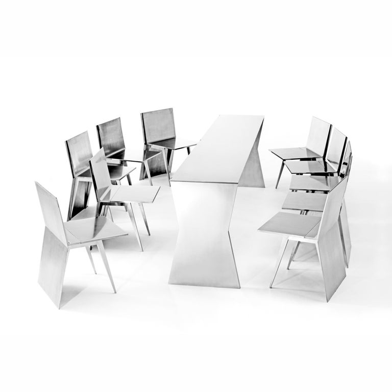Gioia Meller Marcovicz   The Monolith   A stainless steel dining ensemble composed of a folding x-shaped profiled table and ten folding chairs. When nested under the rectangular top, the chairs create a monolithic block.    This extraordinary